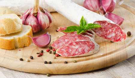 Salami sliced on wooden table photo