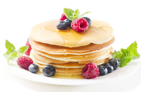 pancakes with raspberries and blueberries isolated on white