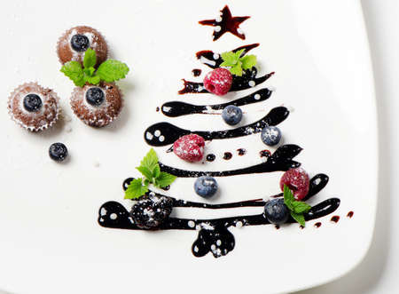 Cupcakes with beriies   and chocolate  christmas tree on a white plate
