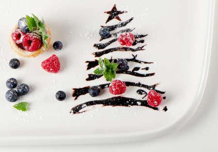 cioccolato natale: dolce albero di Natale con bacche e minton un piatto bianco