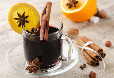 mulled wine with spices  and orange on a wooden table photo