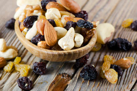 Dried fruits and nuts on a wooden table. Selective focus photo