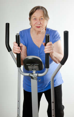 Senior woman on stationary training bicycle photo