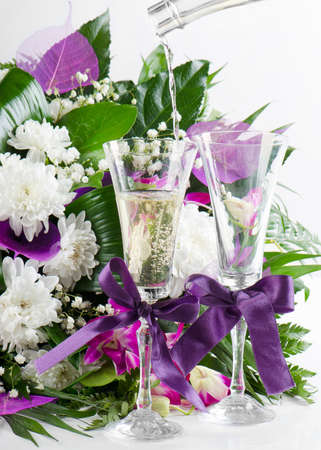 beautiful fresh flowers bouquet and pouring champagne photo