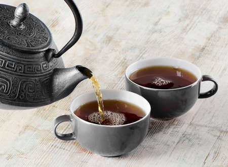 teakettle: Tea being poured into tea cup