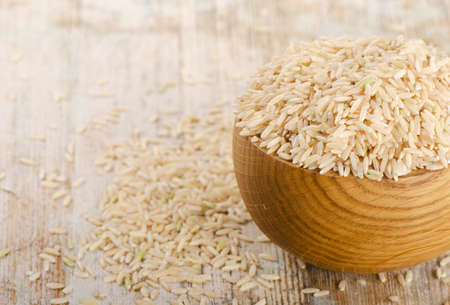 rice grains: brown rice on a wooden table. Selective focus