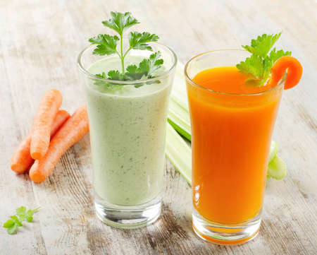 Healthy drinks - Green vegetable smoothie and carrot juice  on a wooden table  selective focus Stock Photo - 20479159