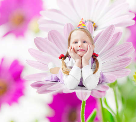 Little happy girl  lying  on spring flower photo
