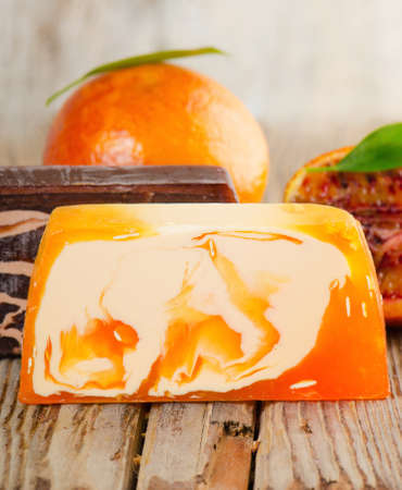 Handmade Soap with fresh orange on a wooden table photo