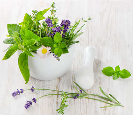 Mortar with fresh herbs on a wooden table photo