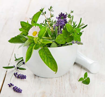 Mortar with fresh herbs on a wooden table