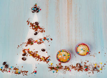 Cupcakes  and   sweet christmas tree  on wooden background photo
