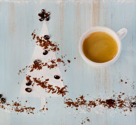 Coffee cup and   sweet christmas tree  on wooden background photo