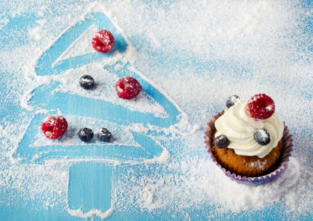 Cupcakes and sweet christmas decorations with fresh beriies photo