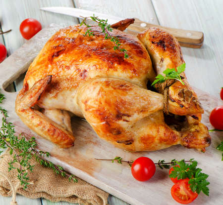 Roasted chicken on wooden table. Selective focus photo