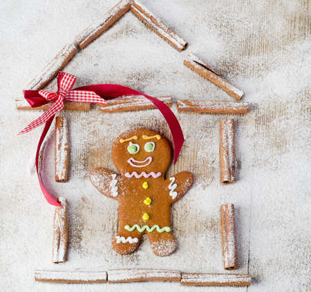 Gingerbread man in house on wooden table photo