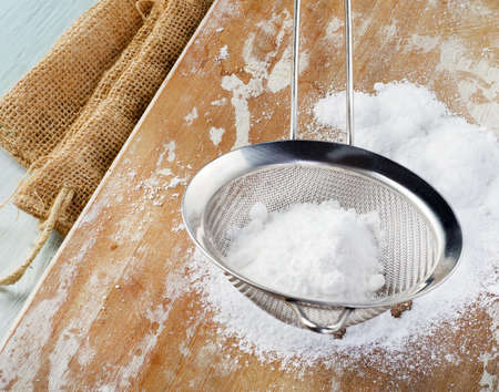 Powdered sugar in a metal sieve on wooden table. Selective focus photo
