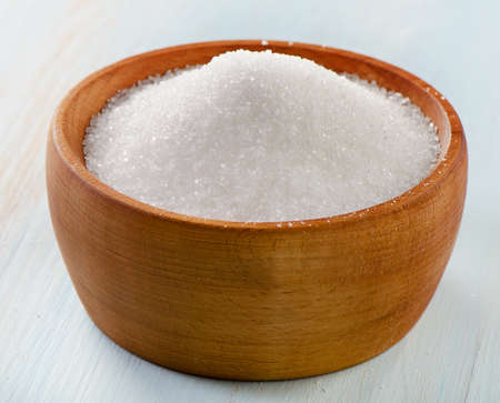 Sugar in wooden bowl  Selective focus