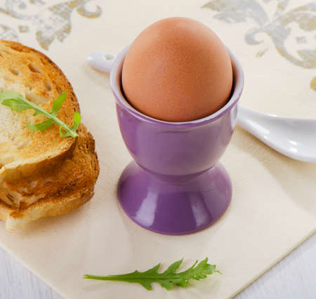 Boiled brown egg in eggcup. Selective focus photo