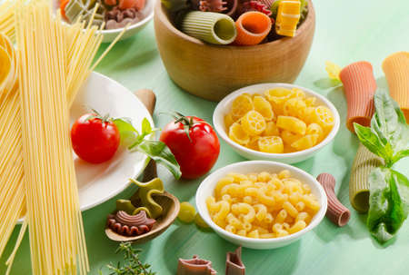 Different types of pasta on a wooden table photo