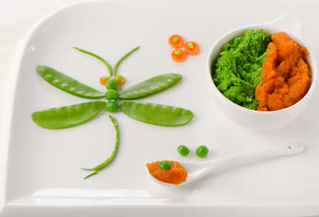 Pureed vegetables for baby with decoration on a white plate. Healthy baby food photo