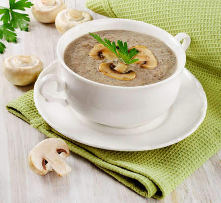 Mushrooms soup in a white bowl. Selective focus photo