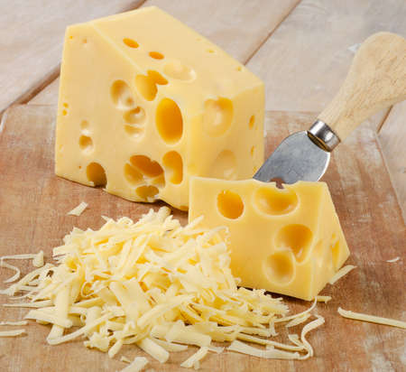 Grated Cheese on a wooden table. Selective focus Stock Photo