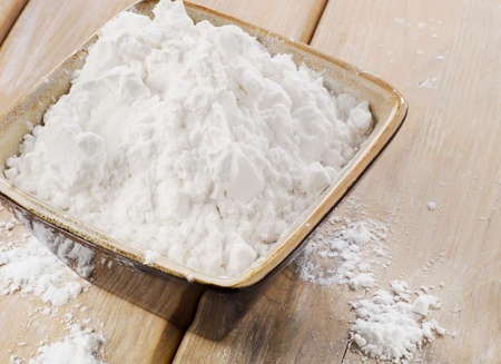 potato starch in a clay bowl on wooden table