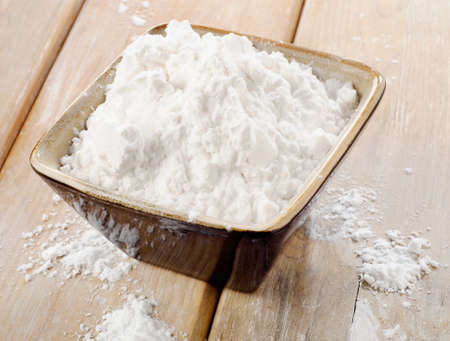 starch: potato starch in a clay bowl on wooden table
