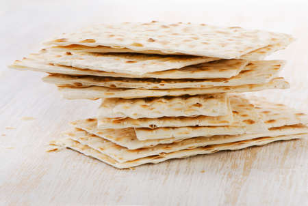 matzos: matzoh - jewish passover bread on a wooden table. Selective focus