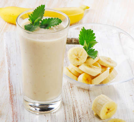 banana: Banana Smoothie on a wooden table. Selective focus Stock Photo