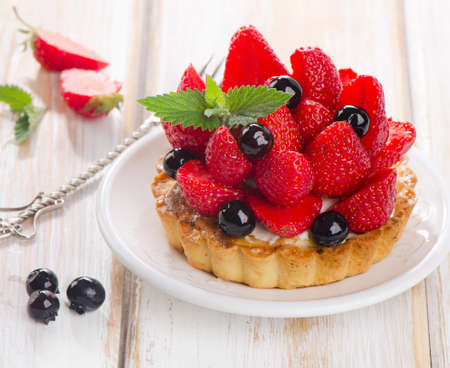 Fresh berries tart on a white plate. Selective focus photo