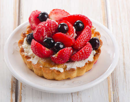 tartlet: Fresh berries cake on a white plate. Selective focus