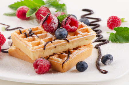 Belgian waffles with blueberries and raspberries. Selective focus photo