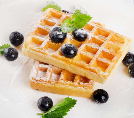 Belgian waffles with blueberries and mint. Selective focus photo