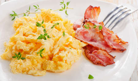 Breakfast - Scrambled eggs and bacon . Selective focus Stock Photo