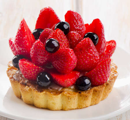 Fresh berry tart on a white plate. Selective focus photo
