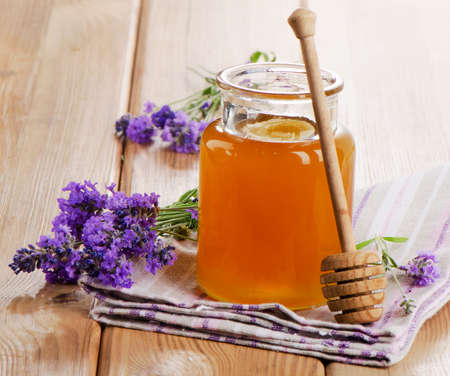 Glass jar of honey with wooden stick and flowers. Selective focus photo