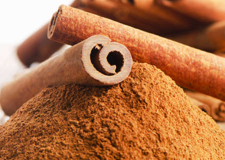 Cinnamon sticks and powder on wooden table. Selective focus photo