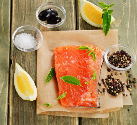 Salmon on a wooden board with lemon and herbs . photo