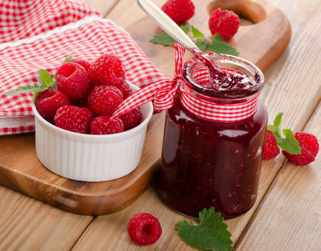 Glass jar of jam with fresh raspberries . Selective focus photo