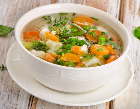 chunky: Vegetable soup in a white bowl. Selective focus Stock Photo