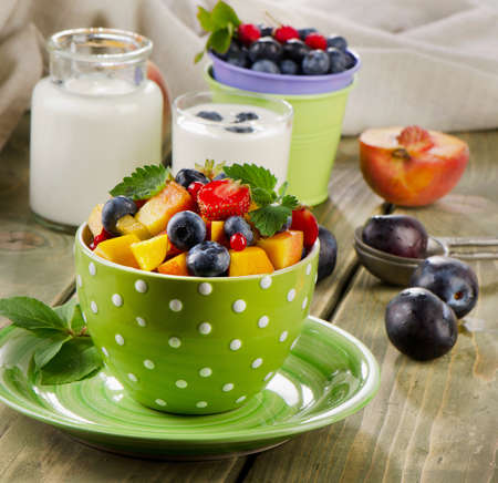 Healthy breakfast - fresh fruit salad and yogurt. Selective focus photo