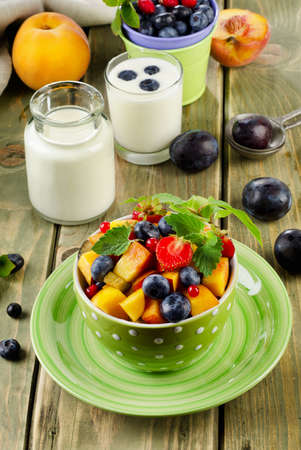 Healthy breakfast - fresh fruit salad and yogurt. Selective focus photo