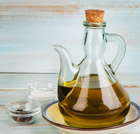 oilcan: Olive oil on a wooden table. Selective focus Stock Photo
