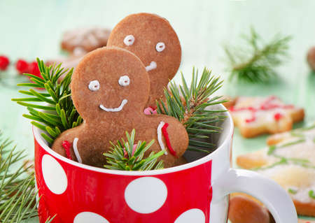 Homemade gingerbread men in red cup. Selective focus photo