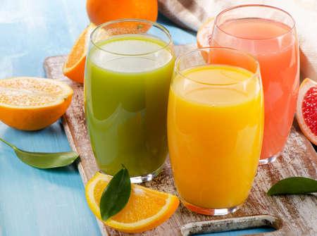 verre de jus d orange: Le jus d'agrumes et de fruits sur fond de bois. Mise au point s�lective