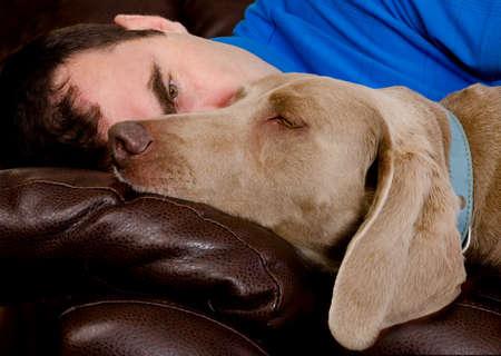 amigos abrazandose: El hombre y su perro que duerme en el sofá