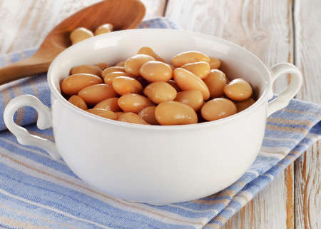 tinned: White beans on a wooden table. Selective focus