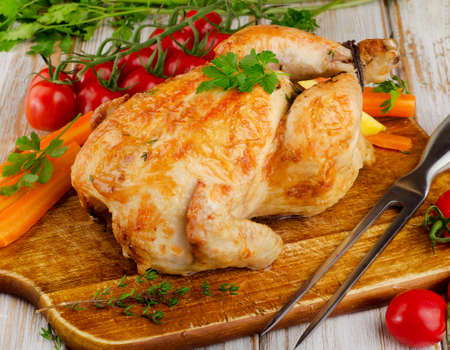 roasted chicken: whole roasted chicken with vegetables on a cutting board.